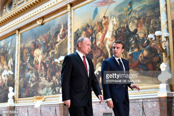 French President Emmanuel Macron speaks to Russian President Vladimir Putin in the Galerie des Batailles as they arrive for a joint press conference...