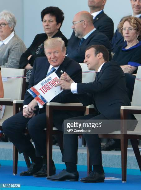 French President Emmanuel Macron speaks to US President Donald Trump as they attend the annual Bastille Day military parade on the ChampsElysees...