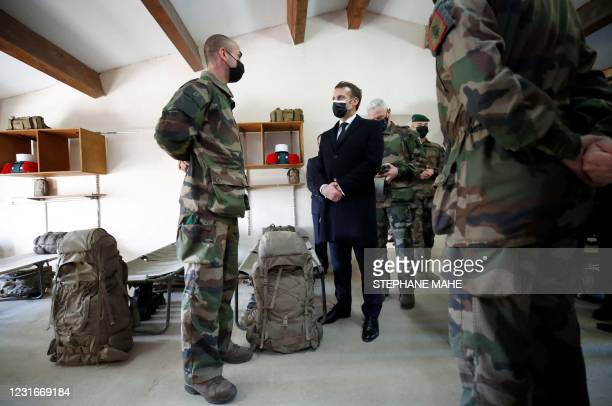 French President Emmanuel Macron speaks with a soldier of the 4th Regiment during a visit at the Ferme du Cuin, the training center of the 4th...