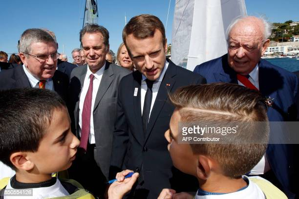French President Emmanuel Macron speaks with children next to Marseille's mayor JeanClaude Gaudin and President of the International Olympic...