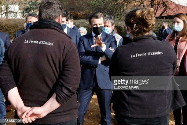 French President Emmanuel Macron speaks with farmers of La Ferme d'Etaules as he visits their farm during an official one-day trip in Burgundy...