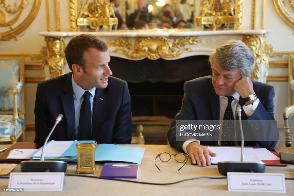 French president Emmanuel Macron (L) speaks with former Environment minister Jean-Louis Borloo, in charge of a mission on the priority neighbourhoods in the French urban policy, during the presentation of a battle plan for the country's most deprived areas, on May 22, 2018 in Paris.