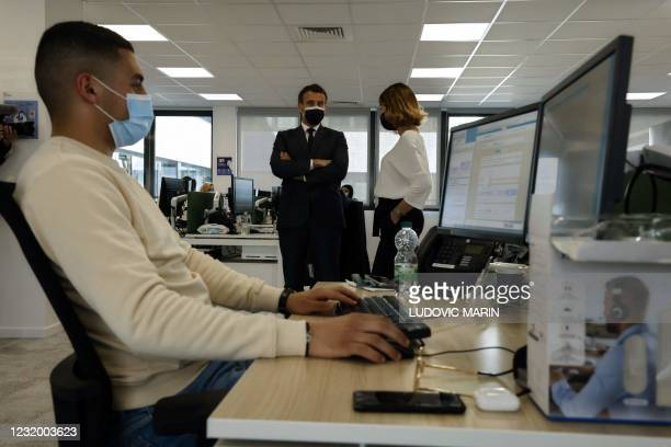 French President Emmanuel Macron speaks with head of partnerships department Christine Navarro as he visits a calling centre of the French Social...