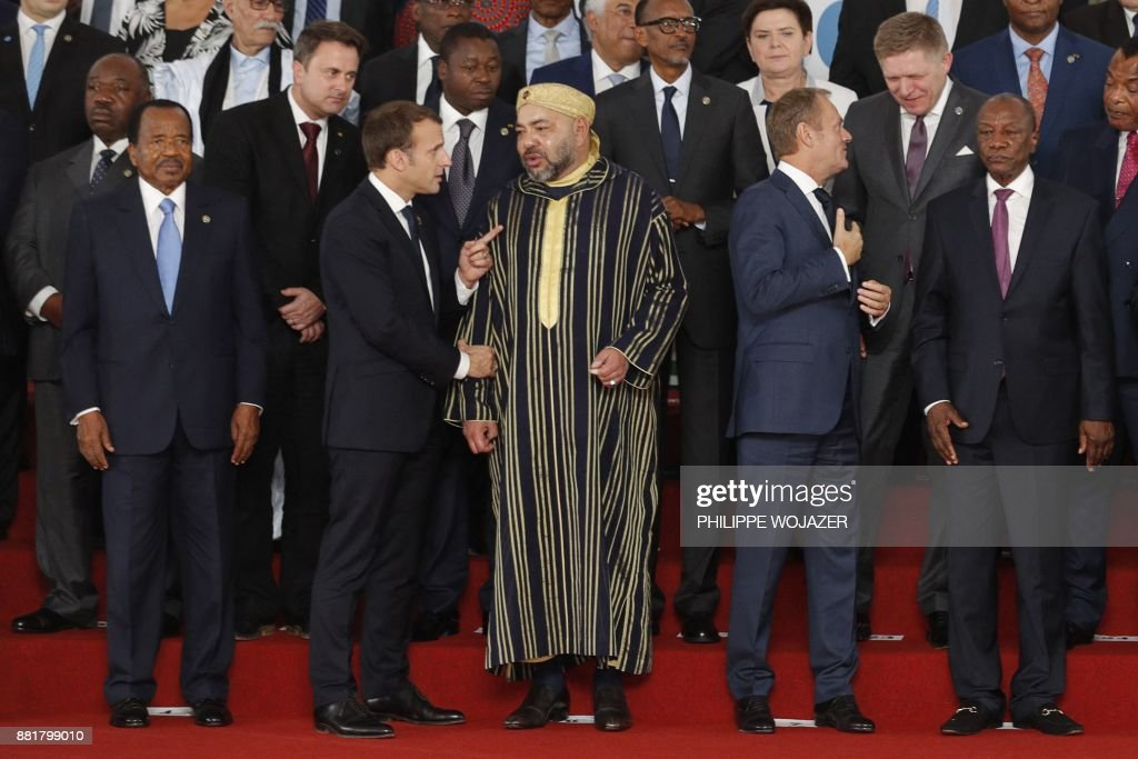 French President Emmanuel Macron (2ndL-bottom) speaks with King Mohammed VI of Morocco (C), next to Cameroon's President Paul Biya (L) and European Council President Donald Tusk (2ndR) standing near, as leaders gather for the family photo during the 5th African Union - European Union (AU-EU) summit in Abidjan, on November 29, 2017. Ivory Coast President opened a Europe-Africa summit on November 29, calling for 'all urgent measures' to end migrant abuses, including slave trading in Libya. /