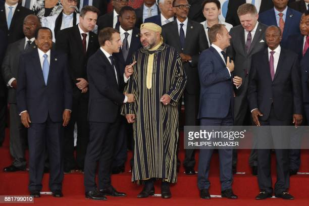 French President Emmanuel Macron speaks with King Mohammed VI of Morocco next to Cameroon's President Paul Biya and European Council President Donald...