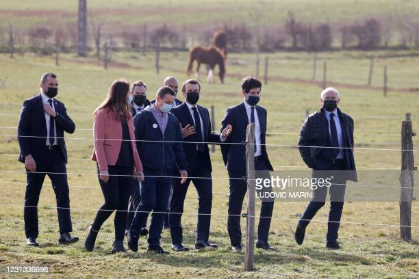 French President Emmanuel Macron speaks with La Ferme d'Etaules' owners as he visits their farm with French Agriculture Minister Julien Denormandie...