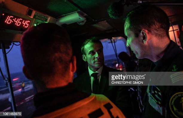 French President Emmanuel Macron speaks with members of the French Navy as he stands on the bridge of the upgraded Charles de Gaulle aircraft carrier...