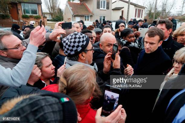 French President Emmanuel Macron speaks with residents as he visits a neighborhood that suffered from flooding after days of heavy rains hit the...