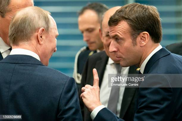 French President Emmanuel Macron speaks with Russian President Vladimir Putin before a meeting at the Chancellery on January 19 2020 in Berlin...
