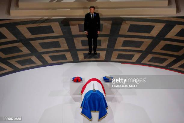 French President Emmanuel Macron stands by the coffin of Late French writer Maurice Genevoix before being inducted to the Pantheon mausoleum where...