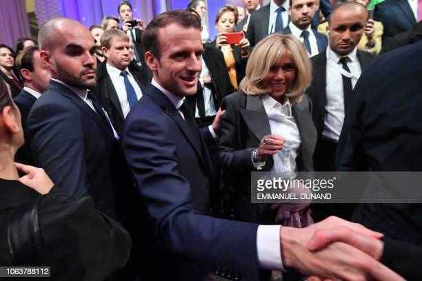 French President Emmanuel Macron stands next to his wife Brigitte Macron as he shakes hands after delivering a speech during a Frenchspeaking...