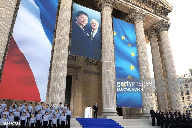 French President Emmanuel Macron stands under a photo of former French politician and Holocaust survivor Simone Veil and her husband Antoine Veil on...