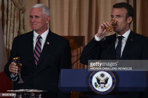 French President Emmanuel Macron takes a drink as US Vice President Mike Pence looks on during a luncheon at the US State Department in Washington DC...
