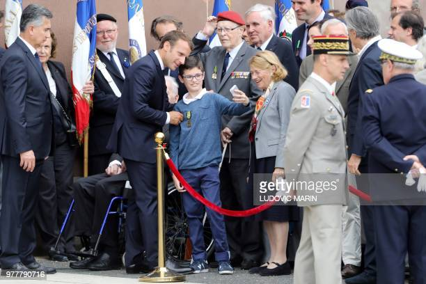 French President Emmanuel Macron takes a 'selfie' with the grandson of a WWII veteran, as he takes part in a ceremony, commemorating General Charles...