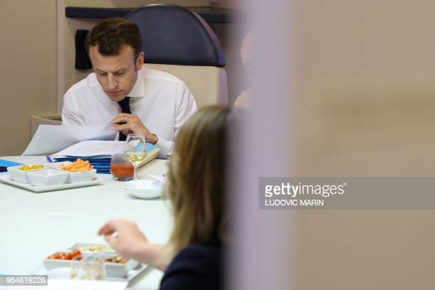 French President Emmanuel Macron takes part in a meeting in his presidential plane Airbus A330 on May 3 2018 during a flight between Sydney and...