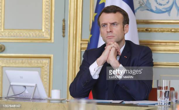 TOPSHOT French president Emmanuel Macron takes part on a videoconference of the economic task force in the green Presidential meeting room at the...