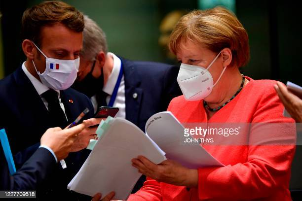French President Emmanuel Macron takes photos with his smartphone from a document held by German Chancellor Angela Merkel during an EU summit in...