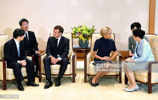 French President Emmanuel Macron talks with Emperor Naruhito while his wife Brigitte talks with Empress Masako during their meeting at the Imperial...
