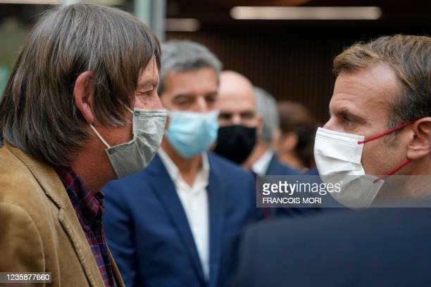 French President Emmanuel Macron talks with former head of the CGT workers Union Bernard Thibault during his visit to the headquarters of the Paris...