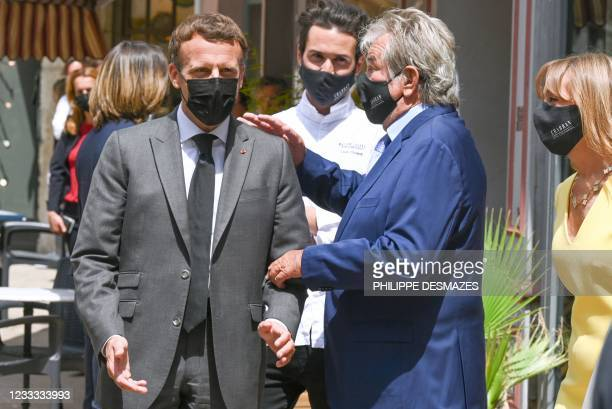 French President Emmanuel Macron talks with restaurant owner Michel Chabran as he arrives for a lunch in Valence, on June 8 during a day visit in the...