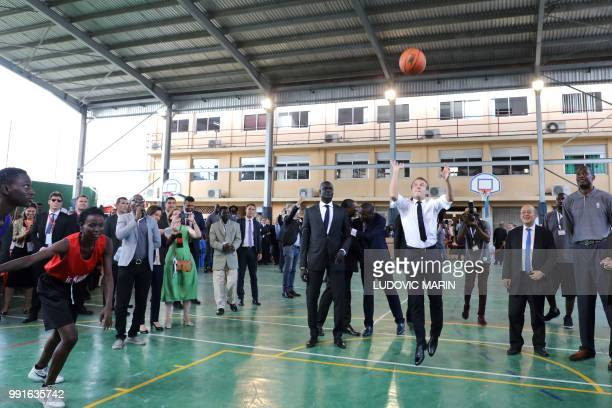 French President Emmanuel Macron throws the ball during a meeting with former pro basketball players from NBA Africa and takes part in a training...