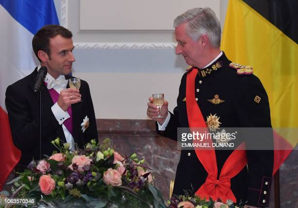 French President Emmanuel Macron toasts to Belgium's King Philippe during a state dinner at the Royal Palace in Laeken Belgium on November 19 during...