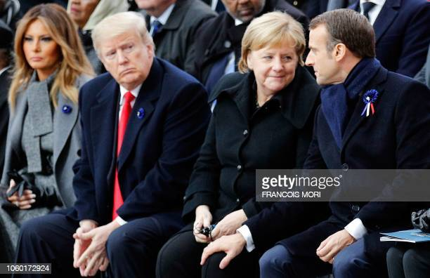 TOPSHOT French President Emmanuel Macron touches the knee of German Chancellor Angela Merkel as they sit next to US President Donald Trump and US...