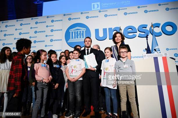French President Emmanuel Macron UNESCO DirectorGeneral Audrey Azoulay and children pose during the 30th anniversary of the Convention on the Rights...