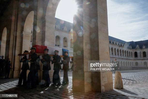 TOPSHOT French President Emmanuel Macron walks behind as French Republican guards carry the flagdraped coffin of late French President Jacques Chirac...