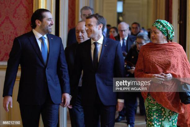 French President Emmanuel Macron walks between Lebanon's Prime Minister Saad Hariri and UN Deputy Secretary General Amina Mohammed as they arrive to...