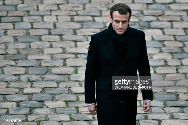 French President Emmanuel Macron walks during a Prise d'armes military ceremony at the Invalides in Paris on November 26 2018