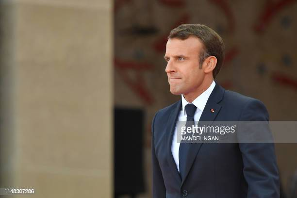 French President Emmanuel Macron walks on stage during a FrenchUS ceremony at the Normandy American Cemetery and Memorial in CollevillesurMer...