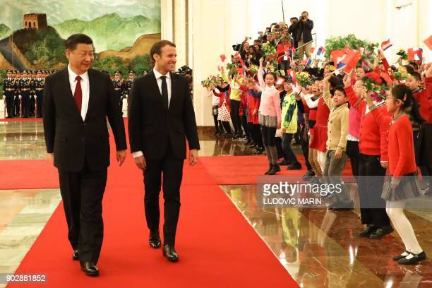 French President Emmanuel Macron walks with Chinese President Xi Jinping as they are greeted by children during a welcome ceremony at the Great Hall...