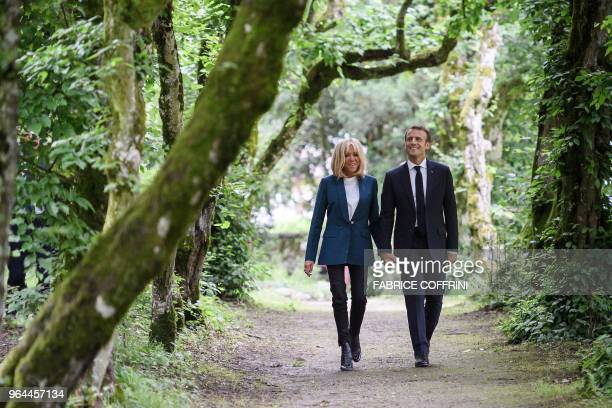 TOPSHOT French President Emmanuel Macron walks with his wife Brigitte Macron in the park of the newly restored Chateau de FerneyVoltaire in...