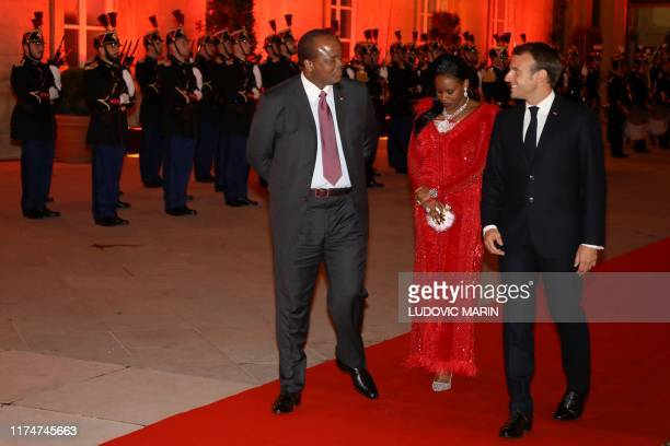 French President Emmanuel Macron walks with King Mswati III Head of State of eSwatini and his wife at Lyon's city hall central eastern France on...