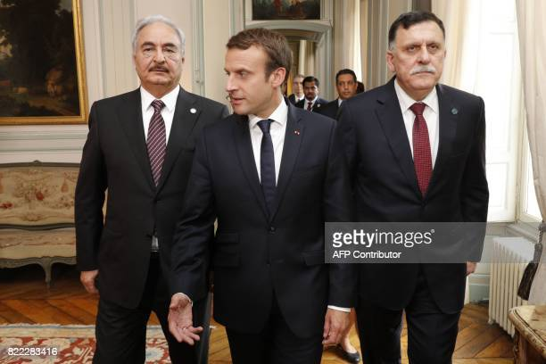 French President Emmanuel Macron walks with Libyan Prime Minister Fayez al-Sarraj and General Khalifa Haftar , commander in the Libyan National Army...