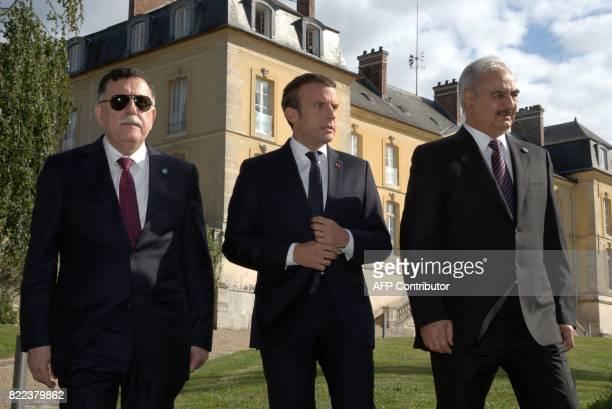 French President Emmanuel Macron walks with Libyan Prime Minister Fayez alSarraj and General Khalifa Haftar commander in the Libyan National Army...