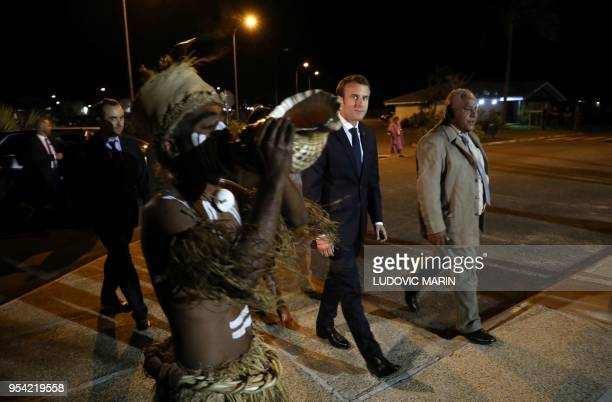 French President Emmanuel Macron walks with President of the 'Senat Coutumier' Pascal Sihaze and others as he arrives to attend a welcoming ceremony...