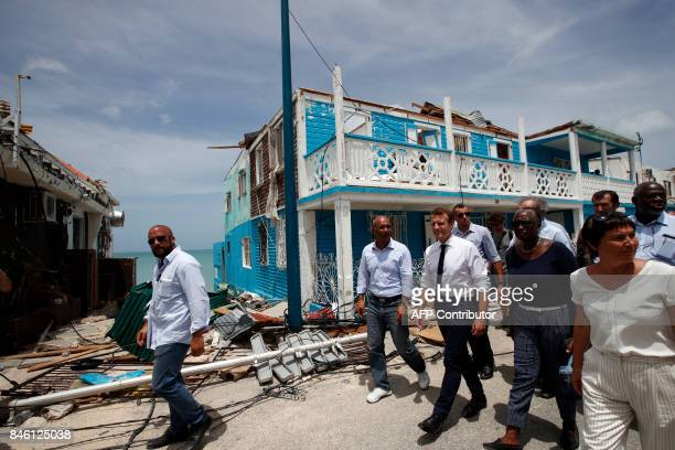 French President Emmanuel Macron walks with residents during a visit to the French Caribbean island of St Martin on September 12 2017 French...