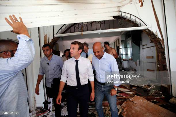 French President Emmanuel Macron walks with residents in the wreckage of a destroyed building during a visit to the French Caribbean island of St...