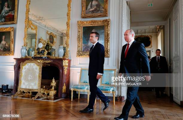 French President Emmanuel Macron walks with Russian President Vladimir Putin at the Chateau de Versailles as they meet for talks in Versailles on May...