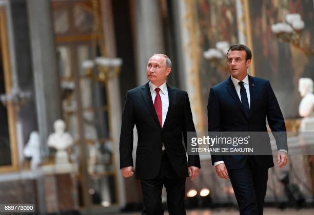 French President Emmanuel Macron walks with Russian President Vladimir Putin in the Galerie des Batailles as they arrive for a joint press conference...