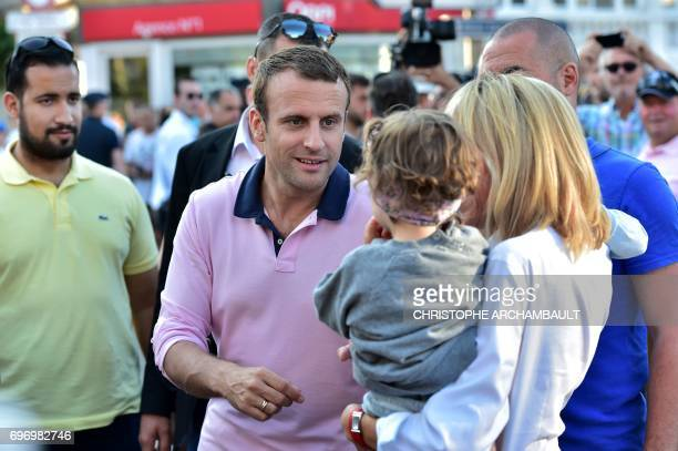 French President Emmanuel Macron watches as his wife Brigitte Macron hold a child on her arm as they greet people in the street at Le Touquet...