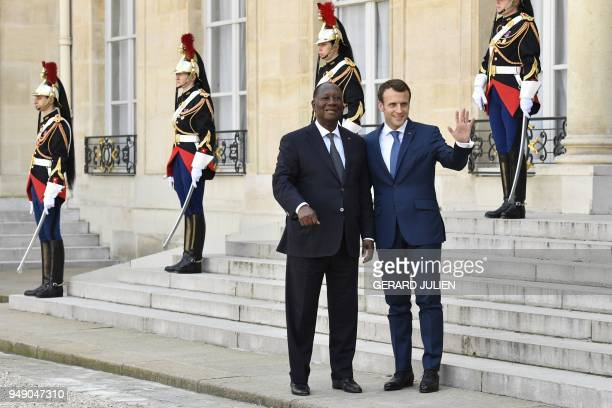 French President Emmanuel Macron waves as he accompanies out Ivory Coast's President Alassane Ouattara after their meeting at the Elysee Palace on...