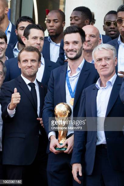 French president Emmanuel Macron waves France's coach Didier Deschamps France's goalkeeper Hugo Lloris pose for a family photo at a reception for the...