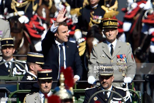 French President Emmanuel Macron waves next to Chief of the Defence Staff of the French Army General Pierre de Villiers as they stand in a military...