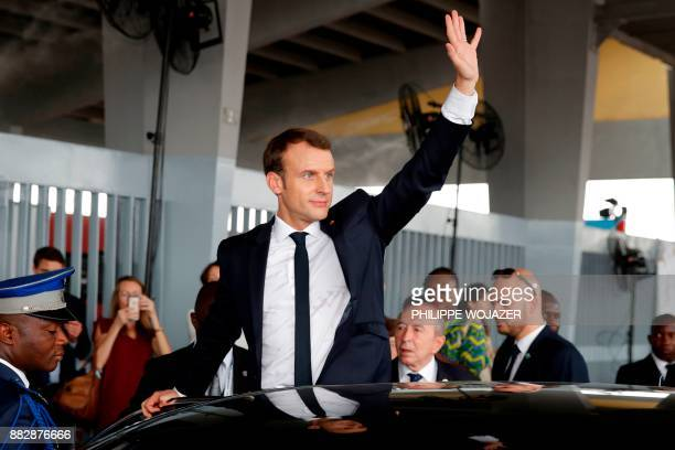 French President Emmanuel Macron waves to people as he leaves a ceremony to start the construction of the first metro line in Abidjan in Abidjan on...