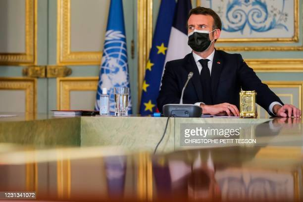 French President Emmanuel Macron, wearing a face mask, attends a video conference meeting held by the United Nations Security Council at the Elysee...