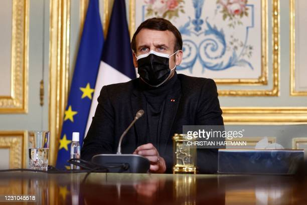 French President Emmanuel Macron, wearing a protective face mask, attends a video-conference meeting with World Health Organization Director-General...