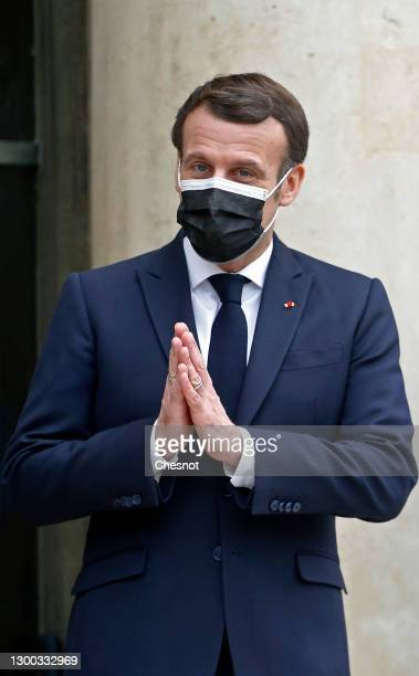 French President Emmanuel Macron wearing a protective face mask gestures as he waits for Moldovan President Maia Sandu prior to a working lunch...